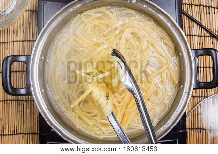 Chef holding boiled spaghetti with tongs / cooking spicy spaghetti concept