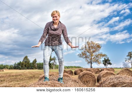 Young woman balancing on hay roll bale