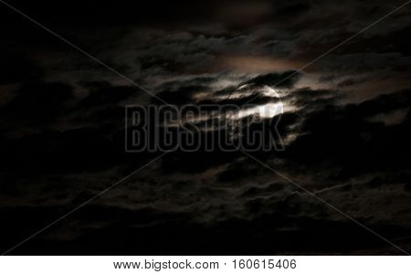 Super bright full moon and partially covered with dramatic black sky clouds.
