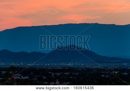 Aerial cityscape of Santa Fe, New Mexico with mountain during pink and blue sunset