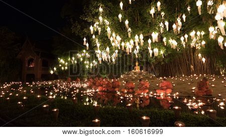 Buddhist Monk Sitting At Waterside With Candle Light In Yeepeng Festival