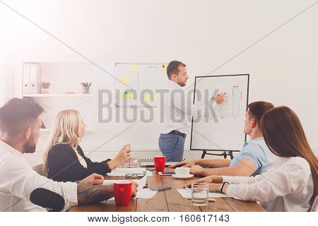 Project presentation. Young happy businessmen and women group in modern office, team discussion at workplace, show information on board. Speech for partners, communication skills