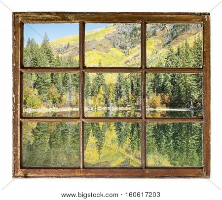 Mountain lake with fall colors as seen  through vintage, grunge, sash window with dirty glass