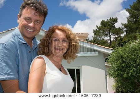 senior and active couple in love in front of the house in summer