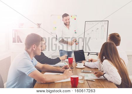 Project presentation. Young happy stylish businessmen and women group at modern office, team discussion at workplace, show information on board. Brainstorming and communication with partners