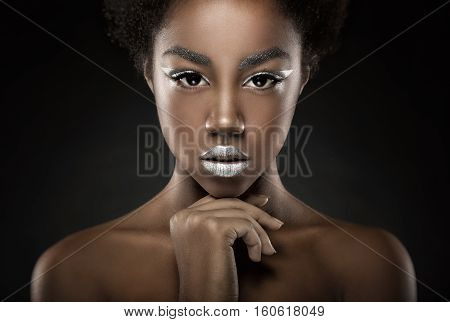 Fashion makeup. Young African American woman with silver make-up on a black background
