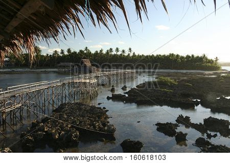 view back to tropical siargao island from cloud 9 surf break across the elevated walkway used to cross the reef