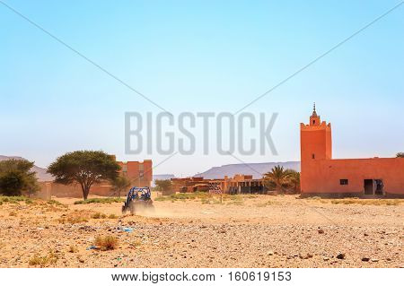 Ramlia Morocco - Feb 26 2016: back view on blue Polaris RZR 800 with it's pilots at the entrance of the small village Ramlia located in the Moroccan desert near a colorful mosque