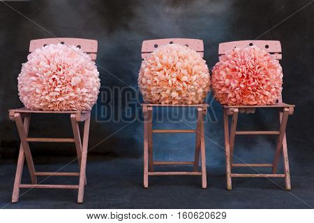 Pink chairs with pink pom poms on a blue background