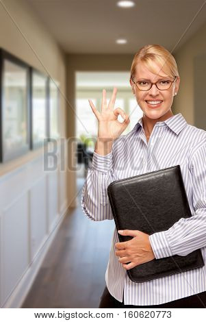 Smiling Businesswoman with Folder and Okay Hand Sign In Hallway of House.