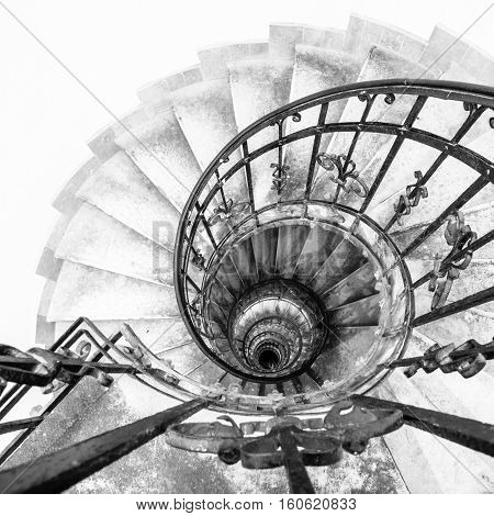 Upside view of indoor spiral winding staircase with black metal ornamental handrail. Architectural detail in St. Stephen's Basilica in Budapest, Hungary. Black and white image.