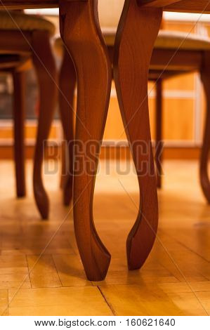 Close-up of curved wooden legs of chairs on parquet.