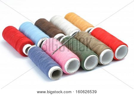 Multicolor sewing threads on white background. Colorful thread spools used in fabric and textile industry