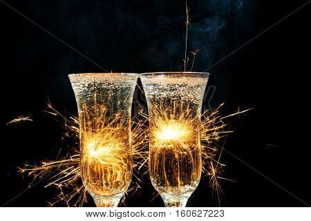 Glasses of champagne and sparklers on bright background with sparklers.