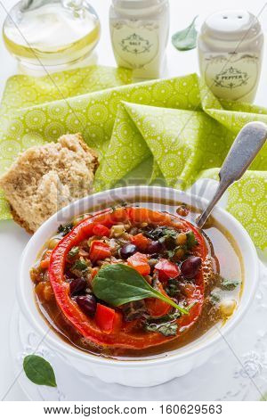 Spiced vegan kidney bean and lentil thick soup with tomatoes and bell pepper. Vintage ceramic bowl on white table.