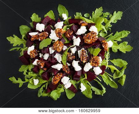 Dietary salad of beets arugula feta cheese and caramelized walnuts with olive oil and lemon juice. Black stone background top view.