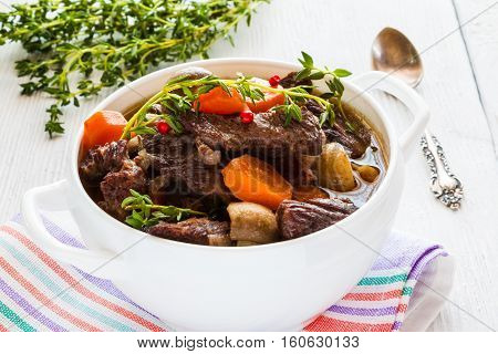 Beef Bourguignon in a white soup bowl. Stew with carrots onions mushrooms bacon garlic and bouquet garni. The dish is served with fresh thyme.