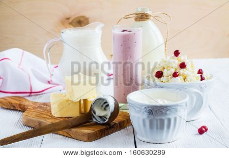 Dairy produce. Milk in bottle cottage cheese in bowl kefir in jar cranberry yogurt in glass butter and fresh berries. Wooden white table.