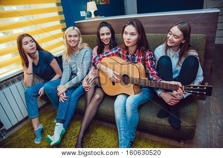 Beautiful girls sitting on couch, have fun and play the guitar in Hostel.