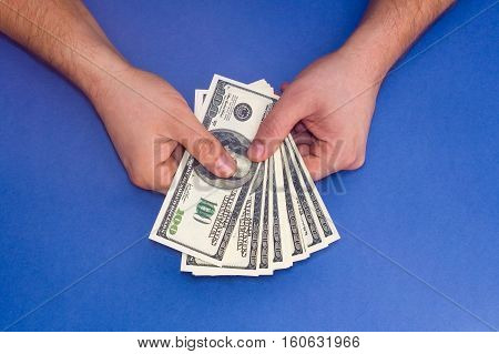 Man counting money on a blue background. Male hand holding a wad of money.