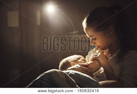 breastfeeding. mother feeding a baby breast in bed dark night