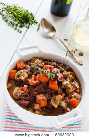 Beef Bourguignon in a casserole on white table. Stewed with bacon garlic carrots onions mushrooms and spices. Bunch of fresh thyme vintage spoon red wine.