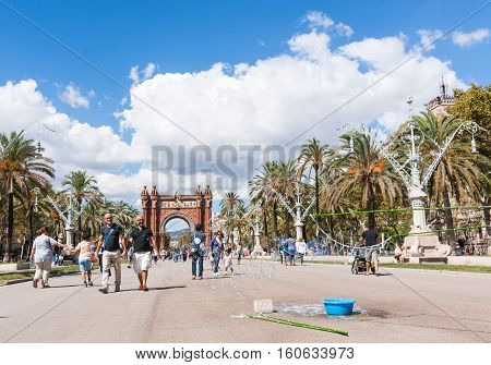 BARCELONA, SPAIN - SEPTEMBER 19, 2016; People and two men holding hands on promenade by Arch of Triumph and children chasing soap bubbles in Barcelona Spain