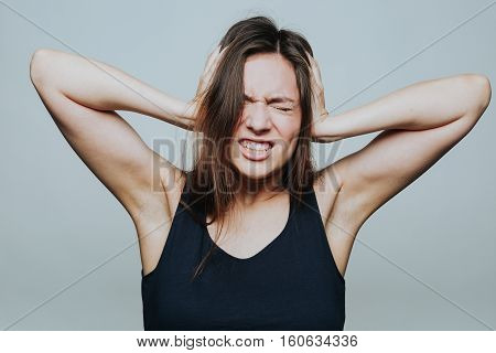 Portrait of young annoyed female in black top covering ears with hands isolated on grey background.