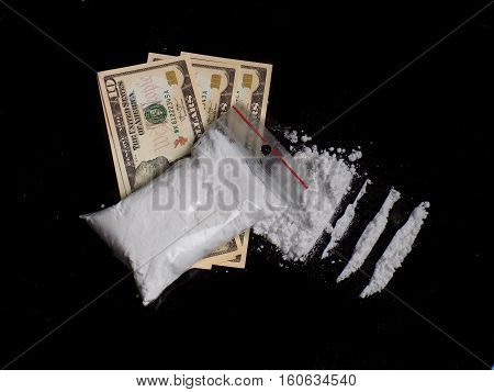 Cocaine drug powder bag on dollar money bills, cocaine pile and lines on black background