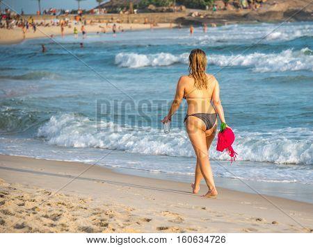 Beach vacation. Beautiful woman in bikini enjoying perfect sunny day walking on the Ipanema beach, Rio de Janeiro, Brazil
