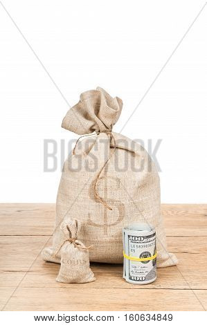 Large bag with money and a small sack with coins near dollars roll on an old wooden table isolated on white background