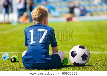 Young Soccer Football Player. Little Boy Sitting on Soccer Pitch. Youth Football Player in Blue Soccer Jersey