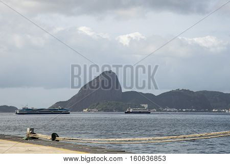 View of the Bay of Guanabara with two boats passing in front of the Sugar Loaf on a cloudy day.