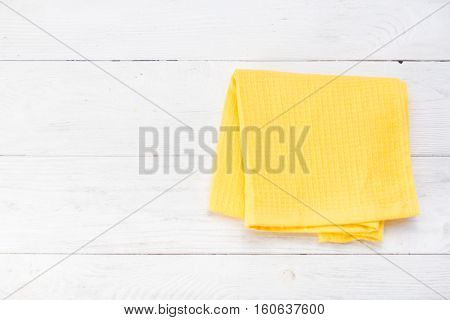 Yellow napkin isolated on white wooden table. Copy space. Top view.