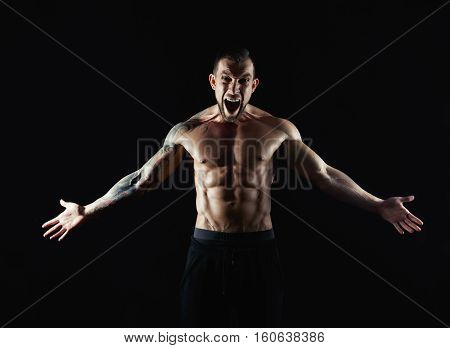 Strong athletic muscular man scream. Emotional male portrait. Half naked with six pack abs bodybuilder. Fitness model.