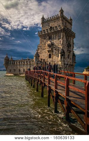 Belem Tower, Lisbon, Portugal with tourists on the bridge