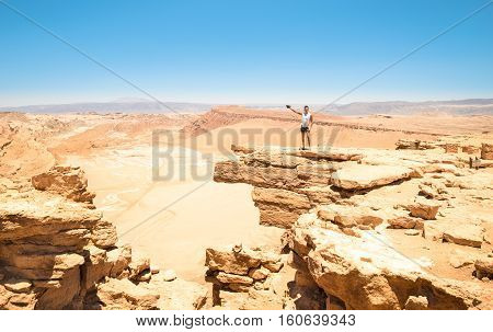 Lonely man with tattoos hiking on rock formation at