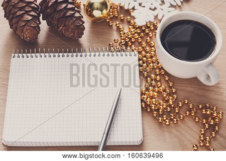 Christmas planning background. Prepare to winter holidays mockup. Top view flat lay of xmas decorations, note papers, pen, black coffee on wood. Copy space for wishlist or shedule