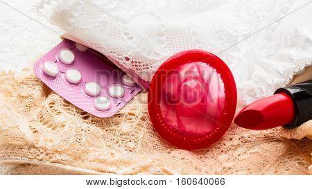 Healthcare medicine contraception and birth control. Closeup oral contraceptive pills condom and red lipstick on lace lingerie.