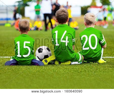 Children Soccer Team Playing Match. Football Game for Kids. Young Soccer Players Sitting on Pitch. Little Kids in Green Soccer Jersey Sportswear