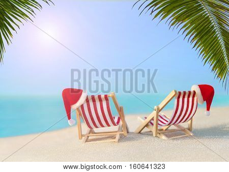 Two striped red-white sunloungers with Christmas Santa hats for romantic couple at ocean sandy sunset beach under big palm leaves New Year travel destinations concept for vacation in hot countries