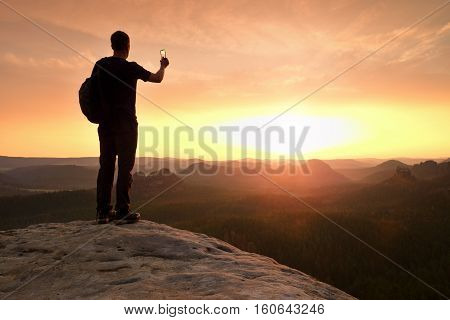Tall Hiker Is Taking Photo By Smartphone On Mountain