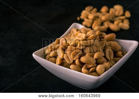 White Square Bowl Full Of Salted Peanuts On Dark Tray