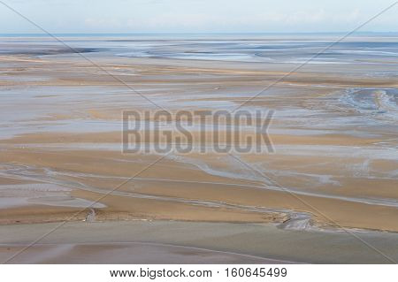 Sea coast at low tide. The tides can vary greatly, at roughly 14m between high and low water marks. One of France's most recognizable landmarks. View from the top of the mount Saint Michael's, France