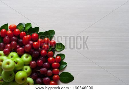 photo of fresh fruit, green apple, grape and cherry tomatoes on a white wooden board