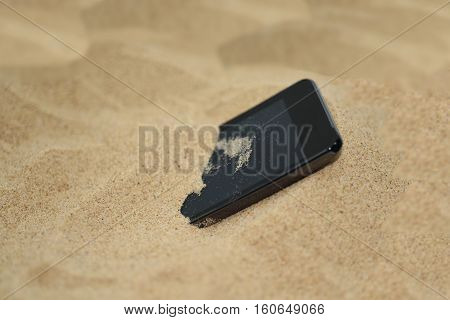 Mobile phone in sand. Isolated abstract macro photo