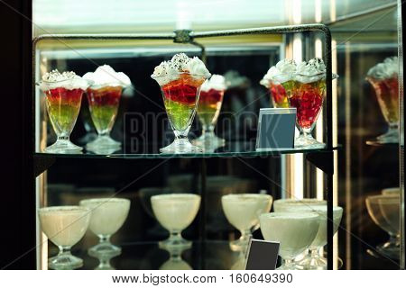 Glass stand with tasty sweets in cafe, close up view