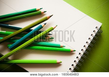 green shades pensils on green paper with notebook