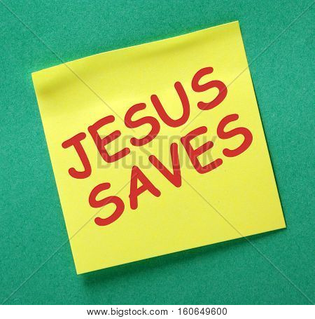 The words Jesus Saves in red text on a yellow sticky note posted on a green noticeboard