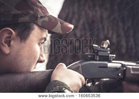 Hunter man aiming and prepared to make a shoot during hunting